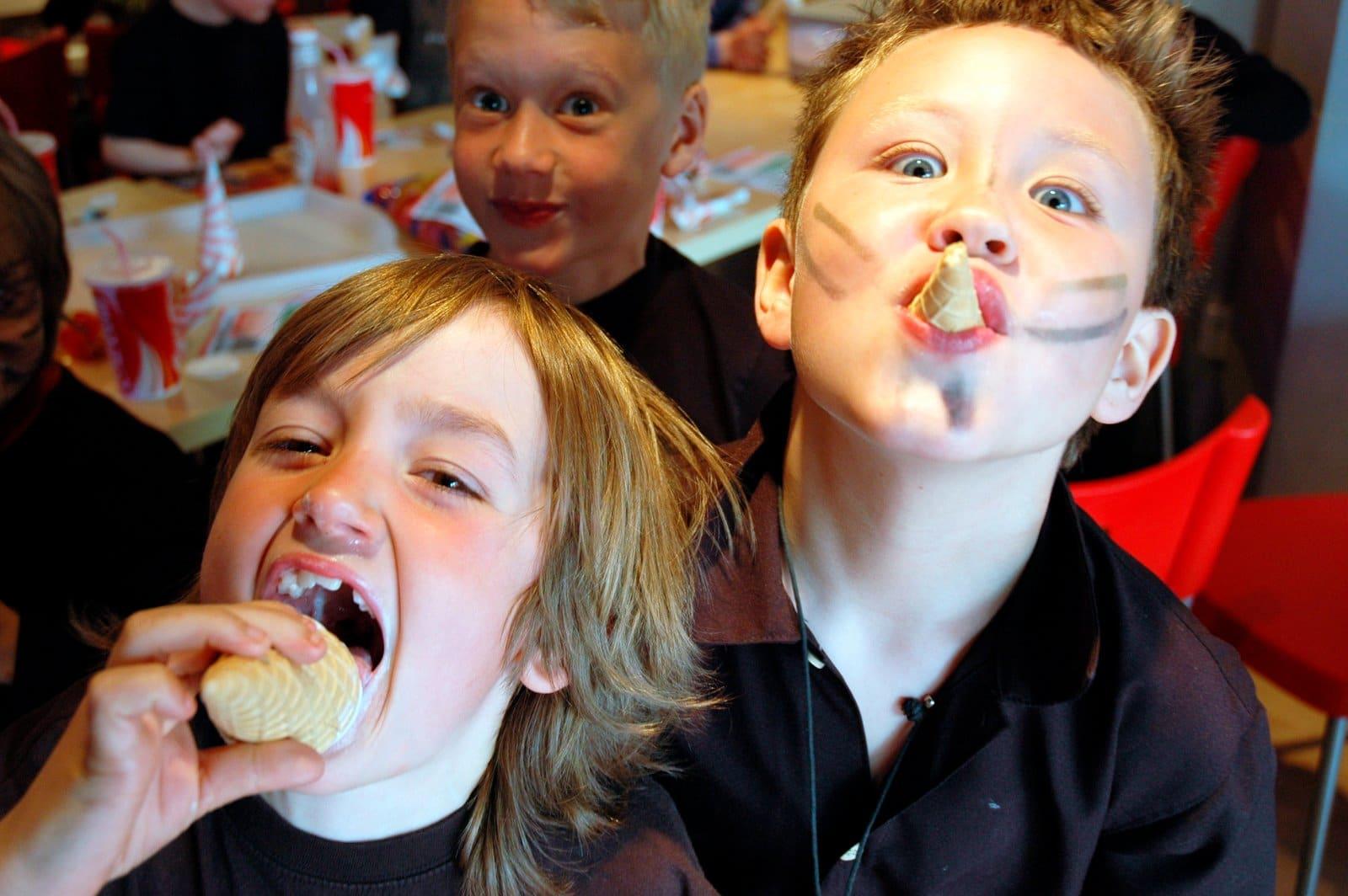 Barn på barnkalas med glass i munnen